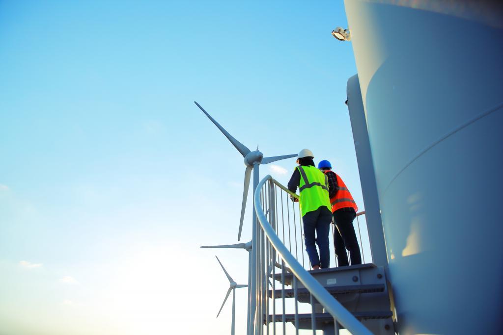 People on the wind turbine, renewable energy, our team